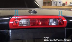 remove the screws holding the middle brake light on Dodge Ram 2008